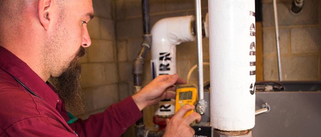 Technician providing heating boiler maintenance