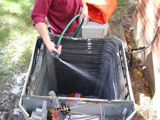 Technician providing air conditioner maintenance