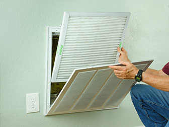 male replacing an air filter in their ventilation