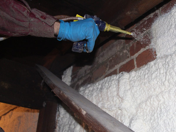 Technician sealing the attic with insulation