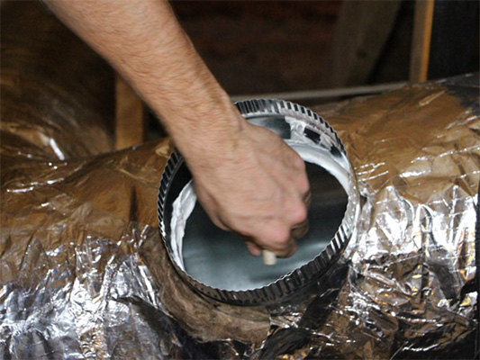 Technician sealing ducts in a home