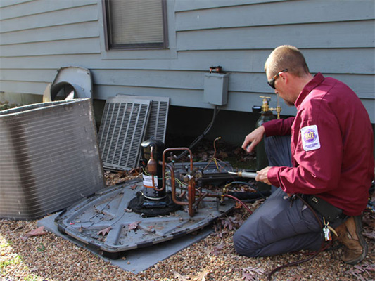 Technician repairing a heat pump