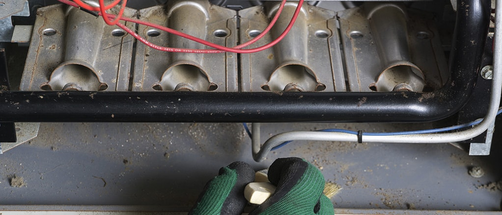 Technician repairing a heat furnace