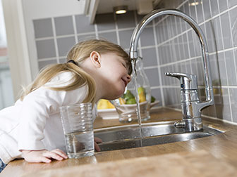 female at a kitchen sink getting water out of the faucet
