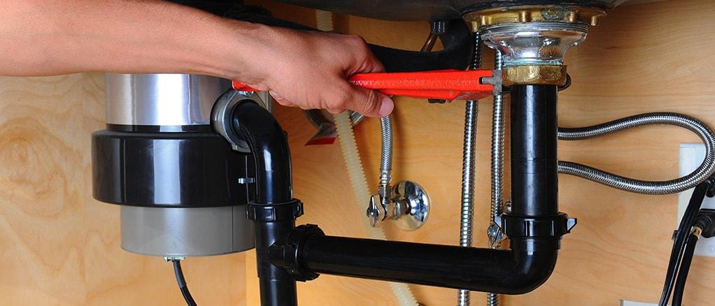plumbing installing a garbage disposal