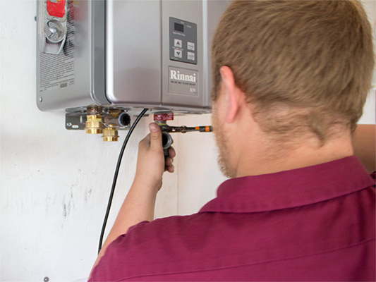 Male technician providing water heater installation