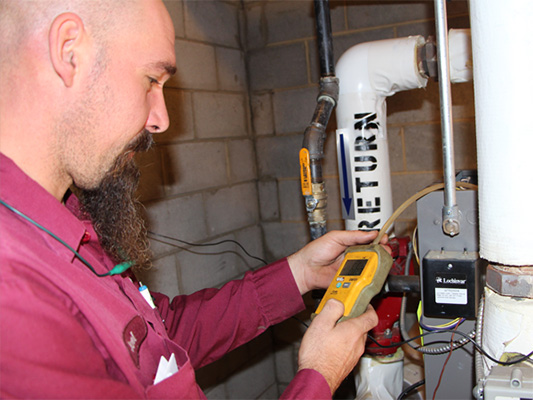 Male technician providing water heater maintenance