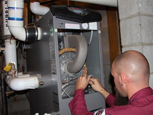 Male technician providing water heater repair