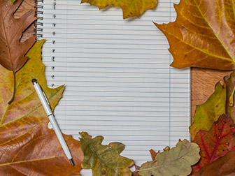 notepad with pen and leaves