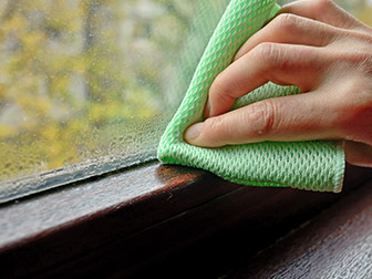 Person wiping window with a cloth because of low humidity