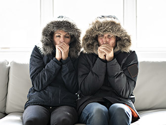 People on a sofa with their winter coats on freezing