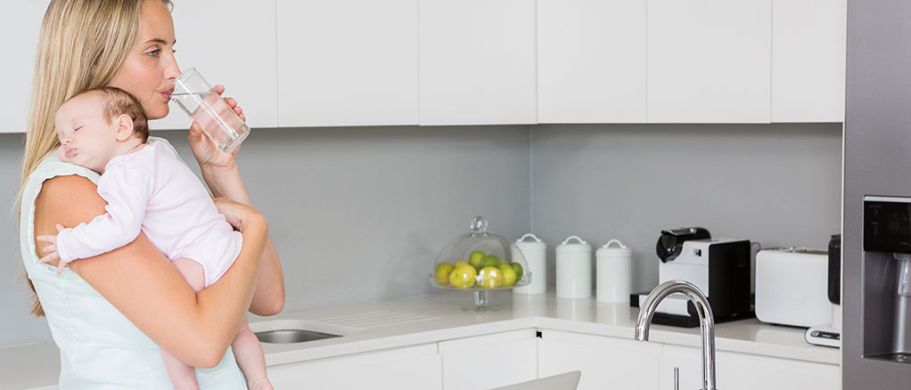 Female with a baby a glass of water in a kitchen