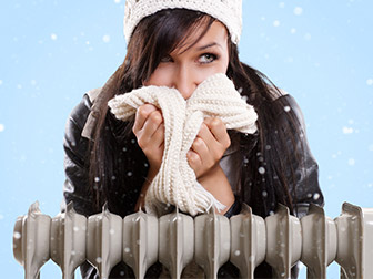 Female with with winter clothing sitting indoors with a portable heater