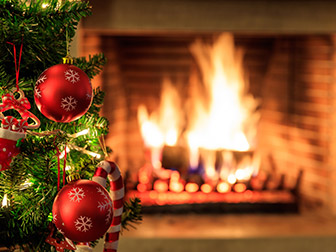 Christmas tree in front of gas logs in fireplace