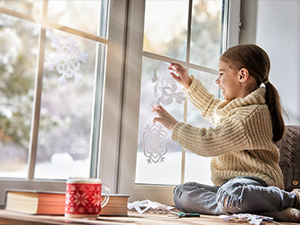Child in a warm house playing with paper snowflakes